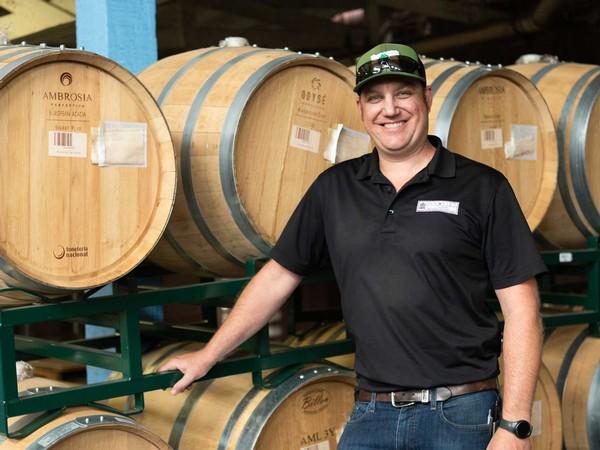 Head Winemaker Chris Graves stands next to wine barrels